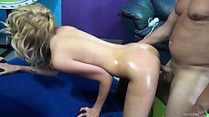 Blondie's oiled up ass is all nice and shiny as she gets fucked from behind