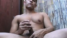 Muscled gay sits outside and jerks off his meat and cums on his thigh