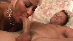 Buxom blonde milf is longing for a young guy's cock and a deep fucking