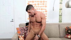 Ripped beefcake takes off his suit and relaxes with a wanking on the couch