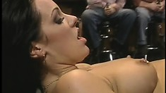 First-class brunette with perky tits has a guy banging her cunt in a crowded place