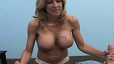 Amateur blonde MILF with big fake hooters takes on a pair of peckers